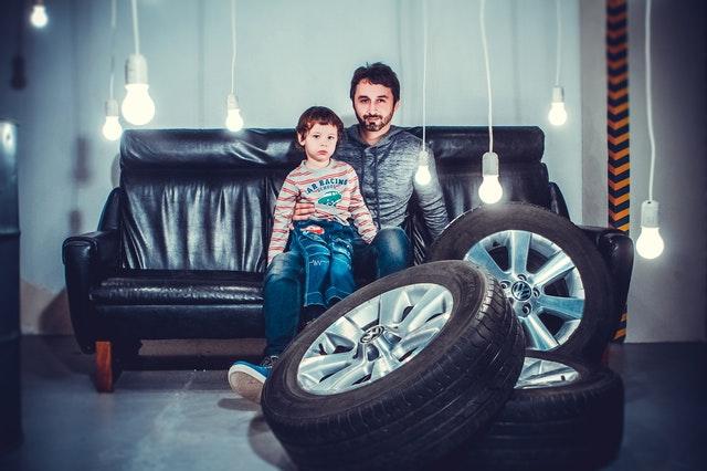 Otec so synom sediaci na gauči v miestnosti s led žiarovkami