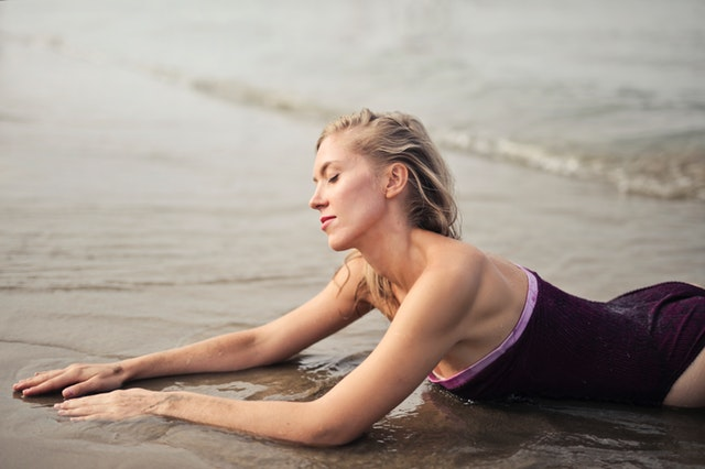 Štíhla žena leží na pláži v piesku.jpg
