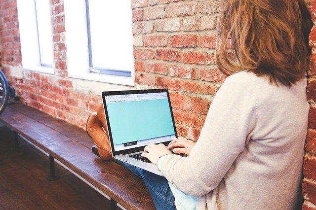 Žena sedí pri okne a píše na počítači