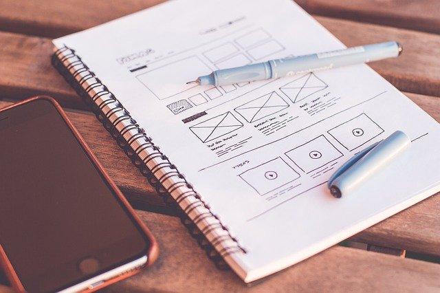 Notes s poznámkami a smartphone na drevenom stole